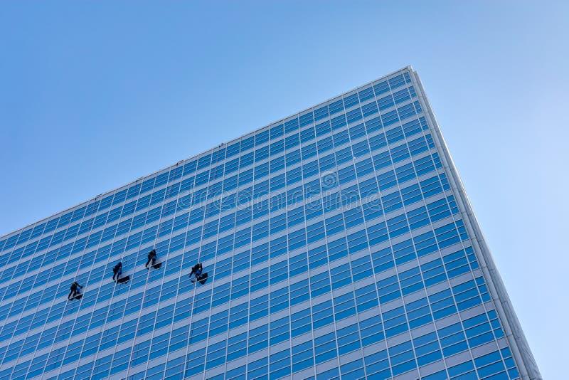Vier Fensterputzer auf der Seite eines Wolkenkratzers lizenzfreie stockfotografie