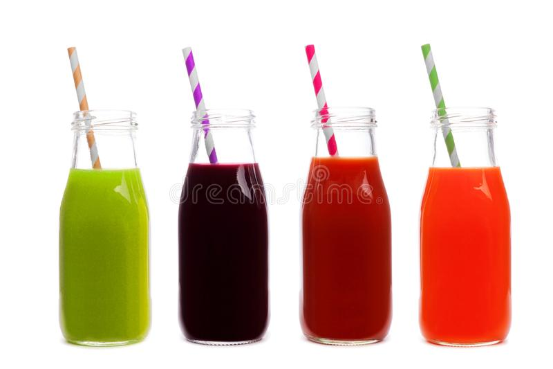 Vier Flaschen des Gemüsesafts, der Grüns, der roten Rübe, der Tomate und der Karotte, lokalisiert lizenzfreies stockbild