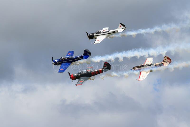 Vier Flugzeuge des Trainers Yak-52 in der Bildung, schleppender Rauch lizenzfreie stockbilder