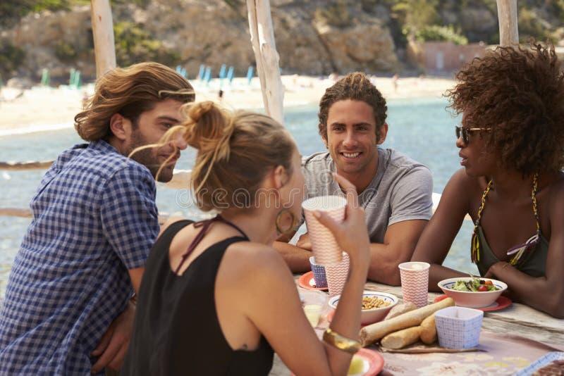 Vier Freunde, die über einer Tabelle an der Küste, Ibiza sprechen lizenzfreies stockfoto