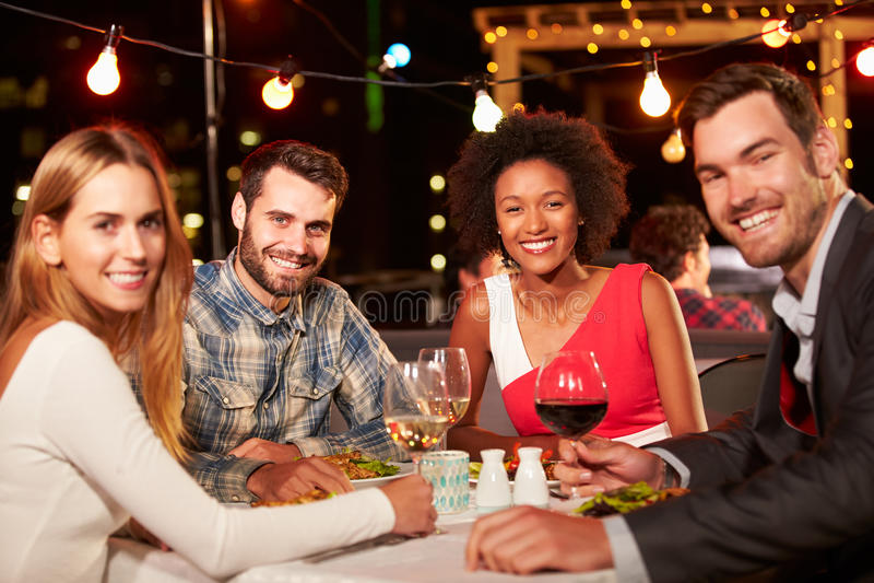 Vier Freunde, die Abendessen am Dachspitzenrestaurant essen stockfotos