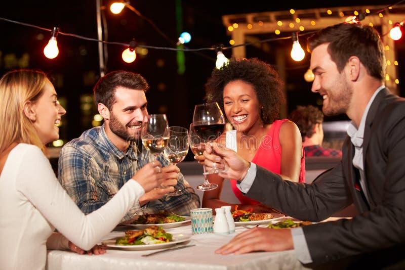 Vier Freunde, die Abendessen am Dachspitzenrestaurant essen lizenzfreie stockfotos