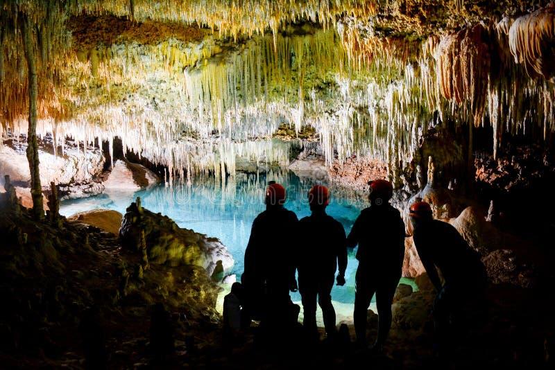 Vier Freunde, die den See in der Höhle betrachten lizenzfreie stockbilder
