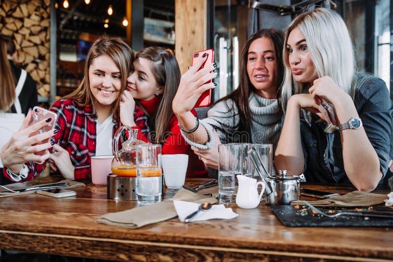Vier Freunde, die durch die Tabelle im Café sitzen und selfie auf Smartphone machen stockfotos