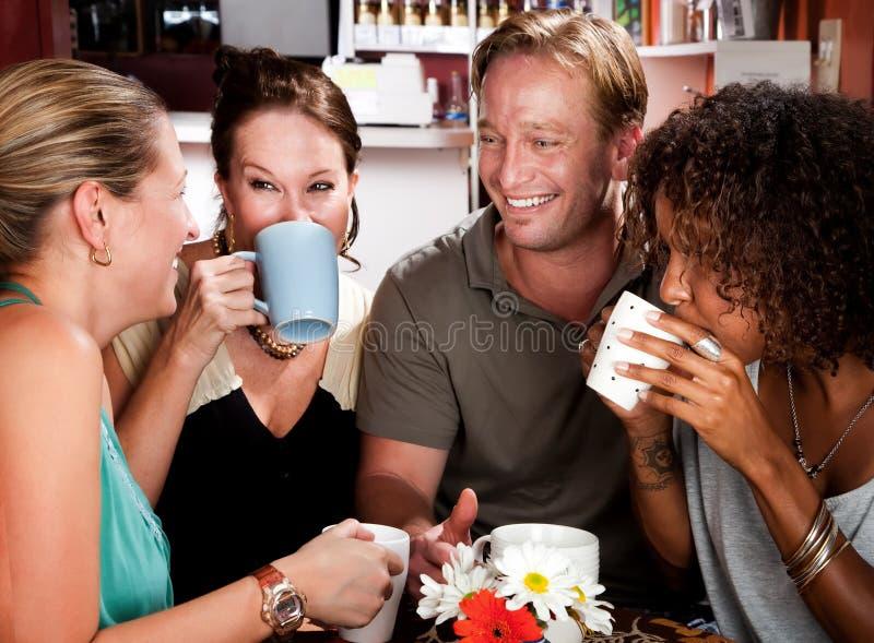 Vier Freunde in einem Kaffee-Haus lizenzfreies stockbild
