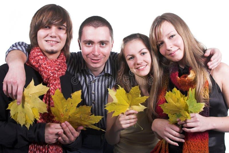 Vier Freunde, Mädchen und Kerle, mit gelbem Ahornholz leav stockbild