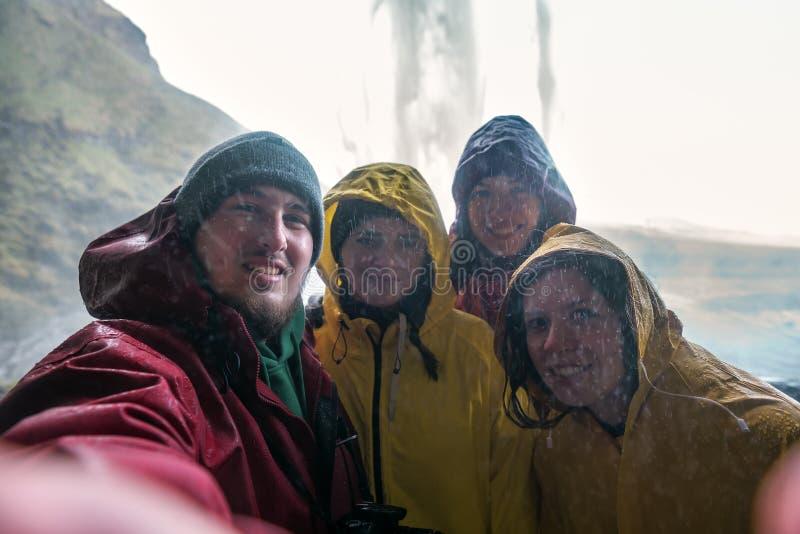 Vier Freunde machen sich ein Selfie unter einem isländischen Wasserfall stockfoto