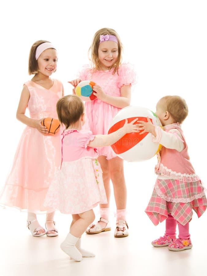 Vier Freunde Spielen eines in den rosafarbenen Kleides lizenzfreie stockfotos