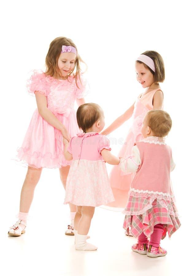 Vier Freunde Spielen eines in den rosafarbenen Kleides lizenzfreie stockfotografie