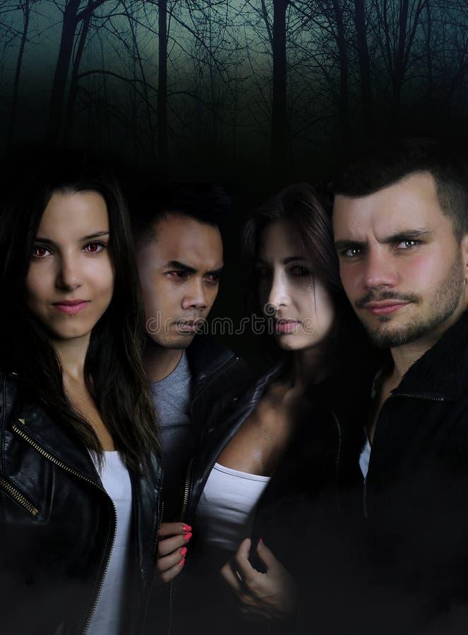 Vier geheimzinnige karakters in een donker bos stock afbeeldingen