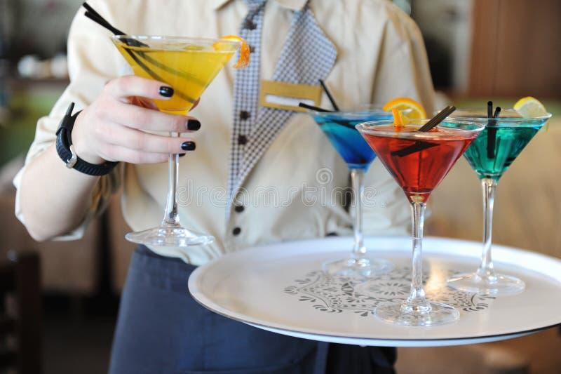 Vier gekleurde cocktails op een dienblad in de handen van de kelner Geel, blauw, groen, rood De kelner heft een geel op stock afbeeldingen