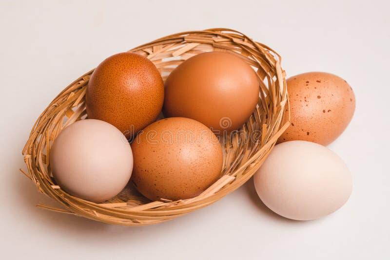 Vier gekleurde kippeneieren in een rieten bruine mand en twee eieren stock foto