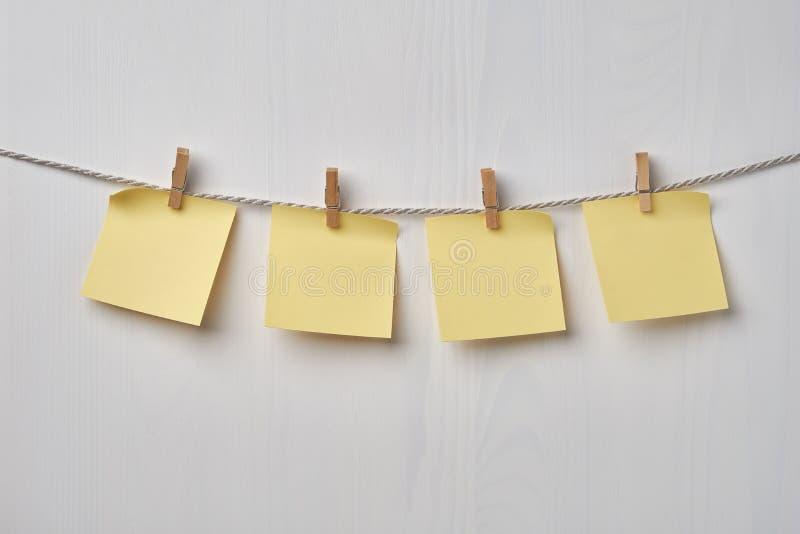Vier gelbe leere Anmerkungen, die am Seil auf weißem hölzernem Hintergrund hängen stockfotografie