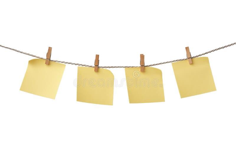 Vier gelbe leere Anmerkungen, die am Seil lokalisiert auf weißem Hintergrund hängen lizenzfreie stockfotos