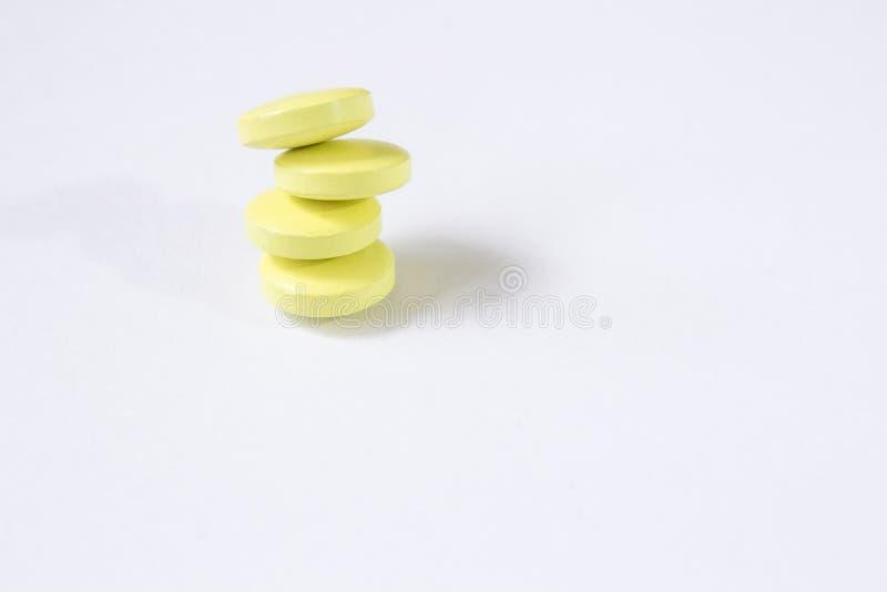 Vier gele tabletten worden gestapeld bovenop elkaar Witte achtergrond royalty-vrije stock foto's