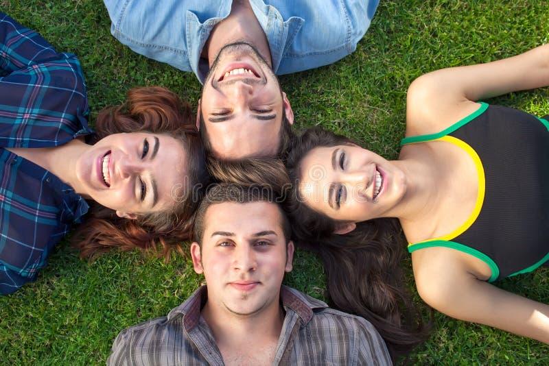 Vier gelukkig tieners het liggen hoofd - - hoofd royalty-vrije stock afbeeldingen