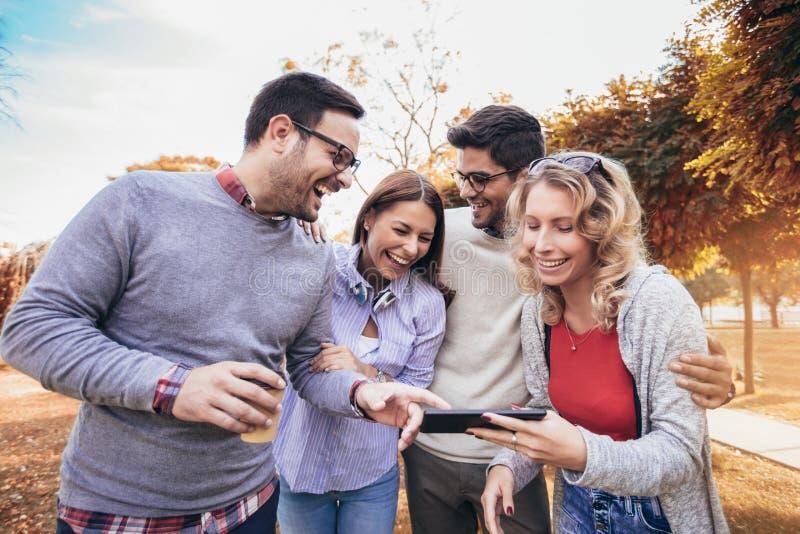 Vier gelukkige glimlachende jonge vrienden die in openlucht in het park lopen die digitale tablet houden royalty-vrije stock fotografie