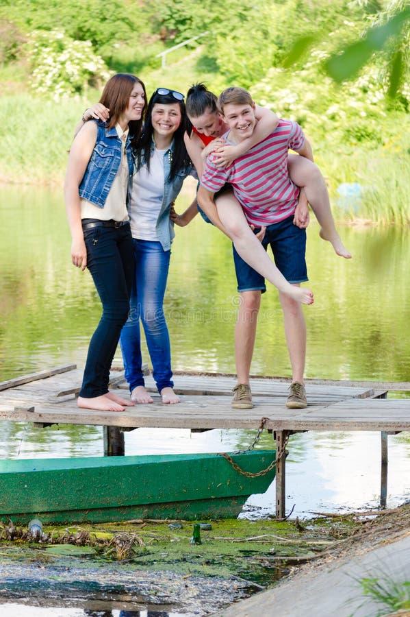 Vier gelukkige glimlachende vrienden hebben in openlucht pret op pijler op de zomerachtergrond stock foto's