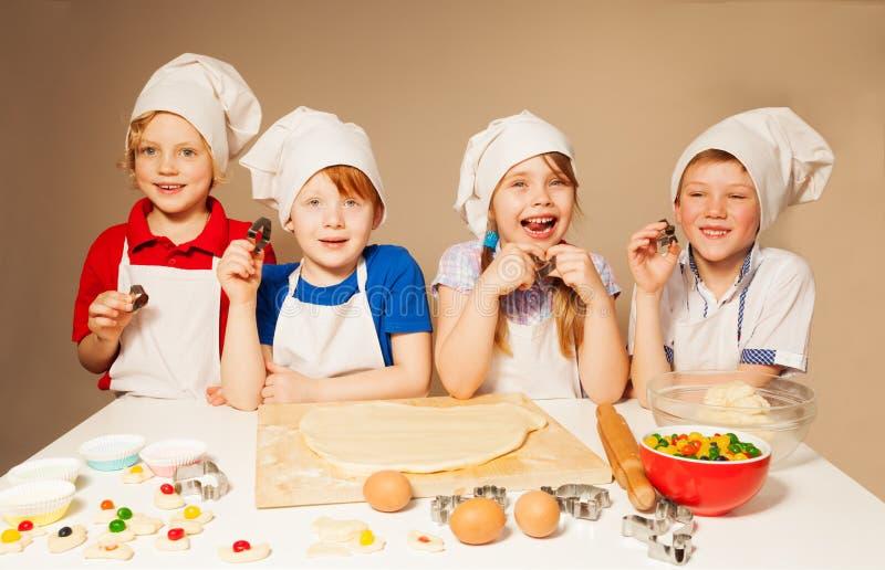 Vier gelukkige kleine chef-koks die bakkers spelen royalty-vrije stock foto