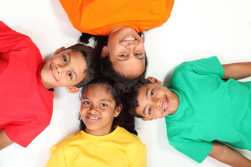 Vier gelukkige schoolvrienden die op vloer samen liggen royalty-vrije stock foto's