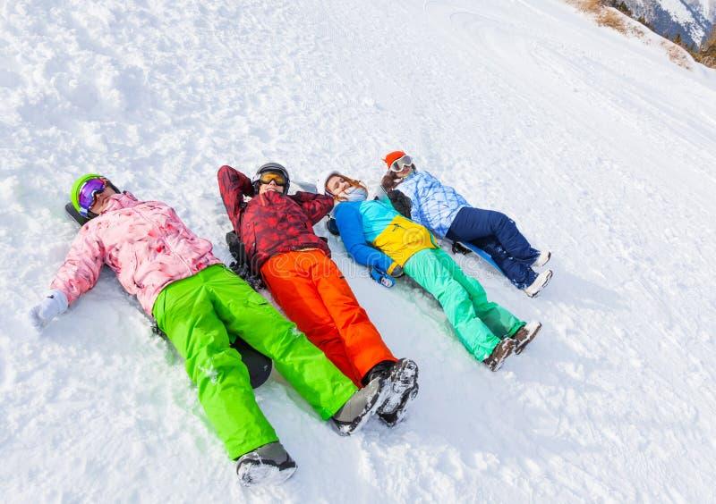 Vier gelukkige snowboarders die op een rij liggen stock foto's