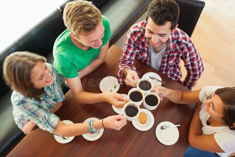 Vier gelukkige studenten die een kop van koffie het babbelen hebben royalty-vrije stock foto's