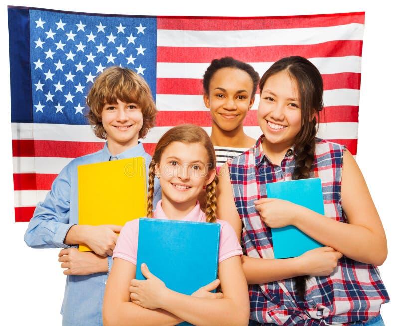 Vier gelukkige studenten die zich tegen Amerikaanse vlag bevinden stock foto's