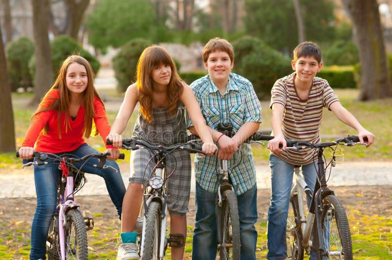 Vier gelukkige tienervrienden die fietsen berijden stock fotografie
