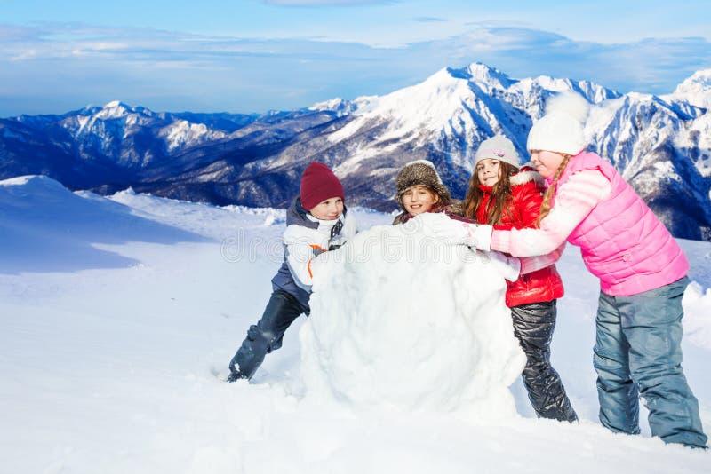 Vier gelukkige vrienden die de sneeuwbal rollen bij de winter stock foto