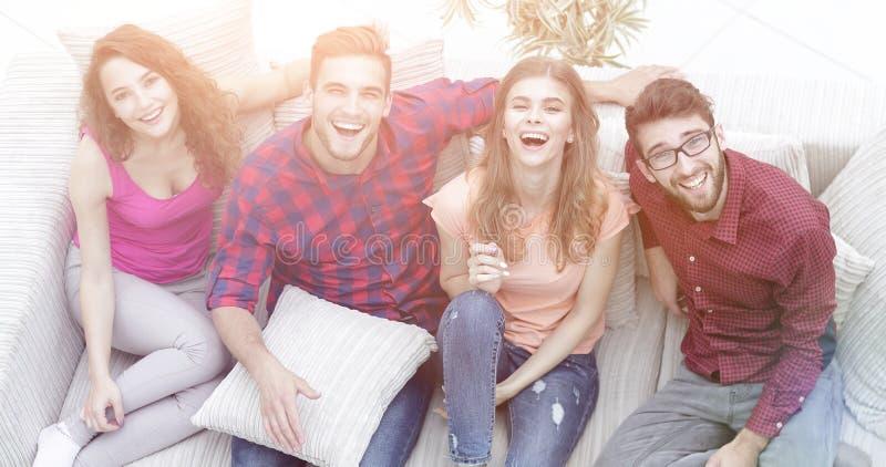 Vier gelukkige vrienden die terwijl het zitten op de laag lachen stock foto
