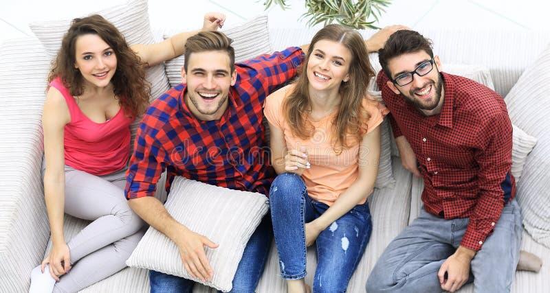 Vier gelukkige vrienden die terwijl het zitten op de laag lachen royalty-vrije stock foto's
