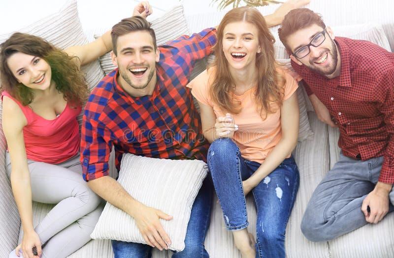 Vier gelukkige vrienden die terwijl het zitten op de laag lachen royalty-vrije stock afbeeldingen