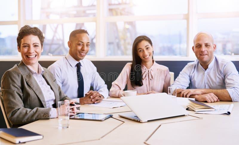 Vier Geschäftsfachleute, welche die Kamera während einer Sitzung betrachten lizenzfreie stockfotografie