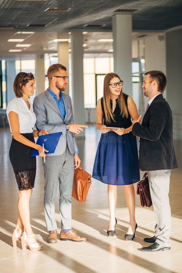 Vier Geschäftsleute, die in der Bürolobby sprechen stockfoto