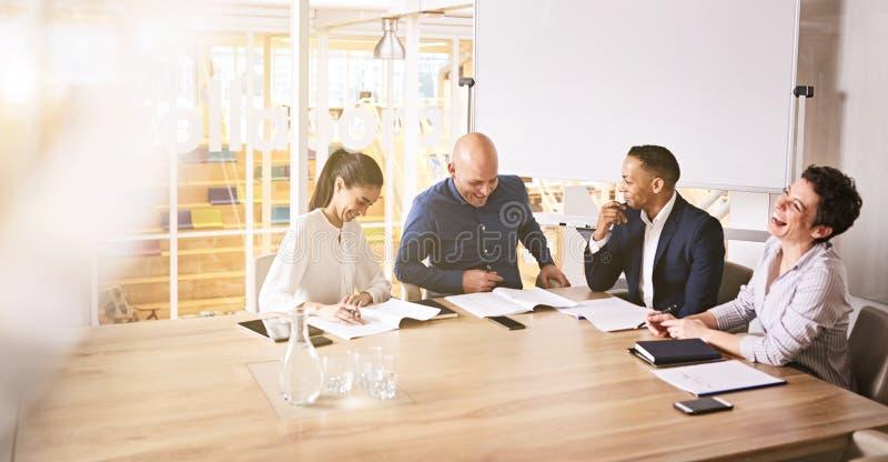Vier Geschäftsleute, die während einer Berufschefetagesitzung lachen stockbilder