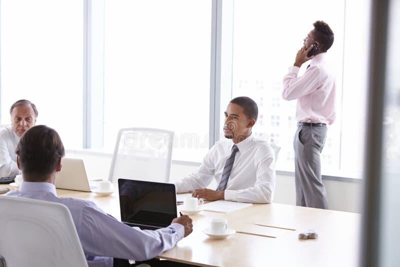 Vier Geschäftsmänner, die Sitzung um Sitzungssaal-Tabelle haben stockfoto