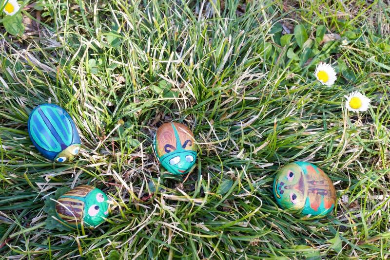 Vier geschilderde stenen als kevers in het groene gras royalty-vrije stock foto