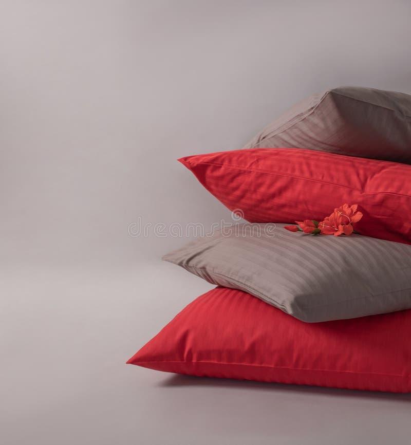 Vier gestapelde kussens met rode bloem tegen de witte achtergrond royalty-vrije stock fotografie