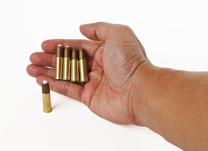 Vier Gewehrkugeln in der Hand getrennt auf weißem Hintergrund stockfotografie