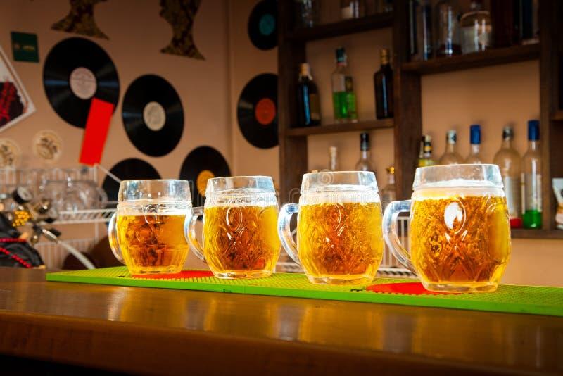 Vier Gläser Bier stehen in Folge auf dem Bartisch lizenzfreie stockfotografie