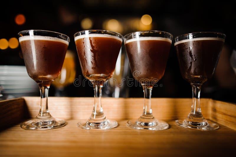 Vier Gläser mit Schokolade-farbigen alkoholischen Cocktails und weißem Schaum lizenzfreie stockbilder