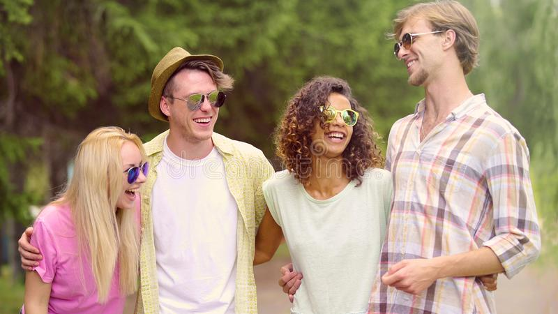 Vier glückliche Freunde, die zusammen herzlichst, interessanter Zeitvertreib, Freundschaft lächeln stockbild
