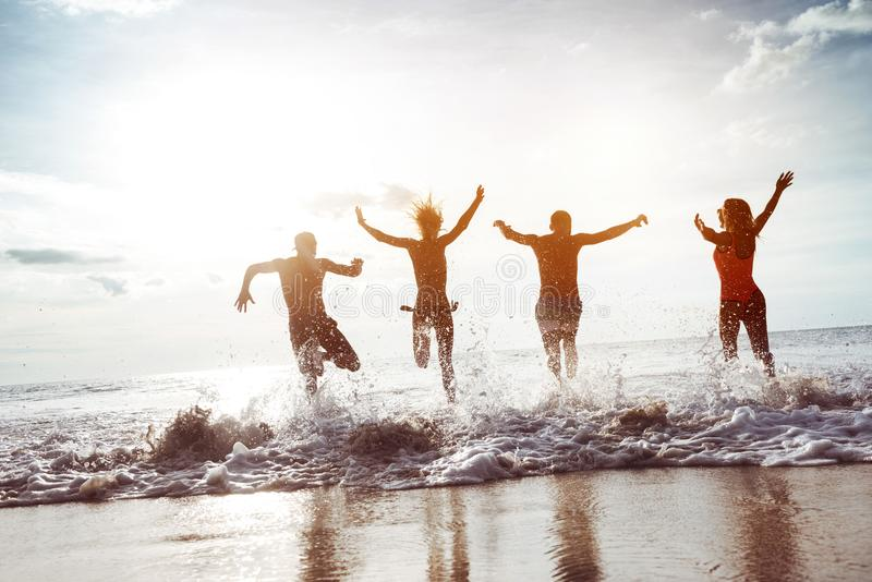 Vier glückliche Freundläufe zum Sonnenuntergangstrand stockfoto
