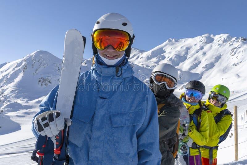 Vier glückliche Freundsnowboarder und -Skifahrer haben Spaß auf Skisteigung mit Ski und Snowboards im sonnigen Tag lizenzfreie stockfotos