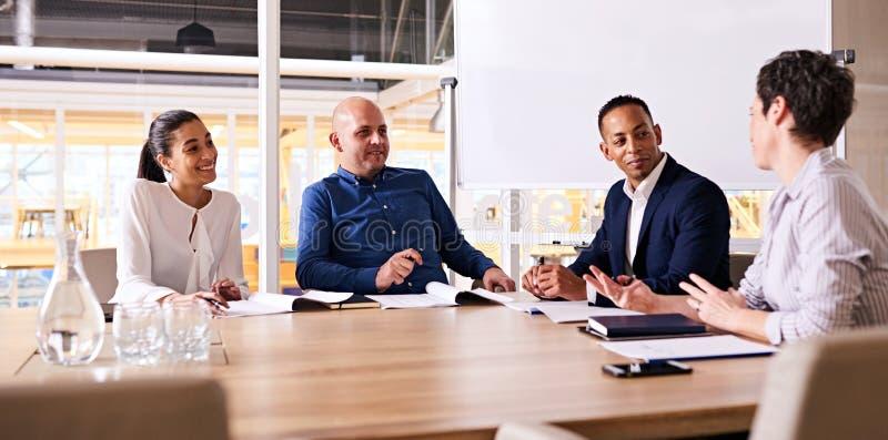 Vier glückliche Geschäftsleute, die während ihres wöchentlichen zusammen sich treffen lächeln lizenzfreies stockfoto