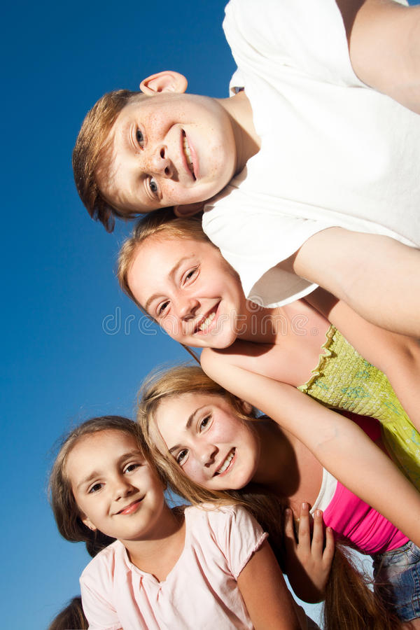 Vier glückliche schöne Kinder, die Kamera von der Spitze am sonnigen Sommertag und am blauen Himmel betrachten Betrachten der Kam stockfotografie