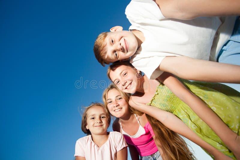 Vier glückliche schöne Kinder, die Kamera von der Spitze am sonnigen Sommertag und am blauen Himmel betrachten Betrachten der Kam lizenzfreies stockfoto