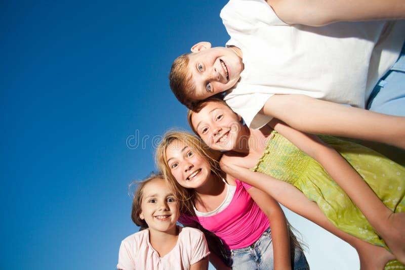 Vier glückliche schöne Kinder, die Kamera von der Spitze am sonnigen Sommertag und am blauen Himmel betrachten Betrachten der Kam lizenzfreies stockbild