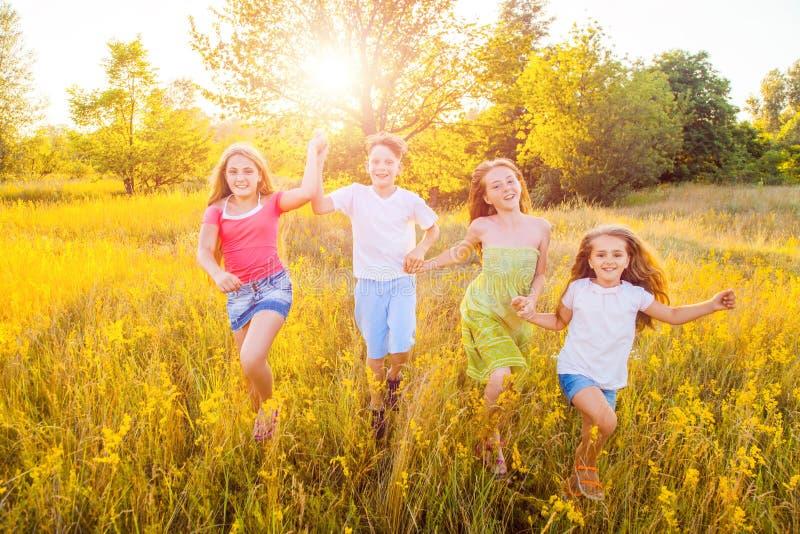 Vier glückliche schöne Kinder, die am schönen Sommertag zusammenrücken spielend laufen lizenzfreie stockfotografie