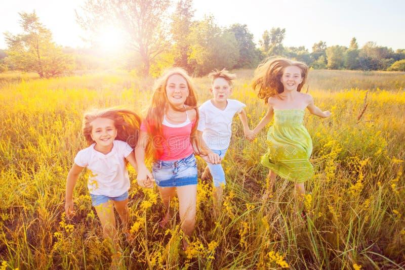 Vier glückliche schöne Kinder, die am schönen Sommertag zusammenrücken spielend laufen stockfoto